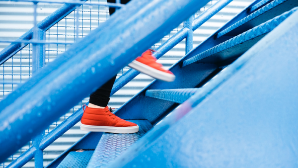 Feet with orange sneakers climbs stairs